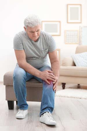 Photo pour Senior man suffering from knee pain at home - image libre de droit