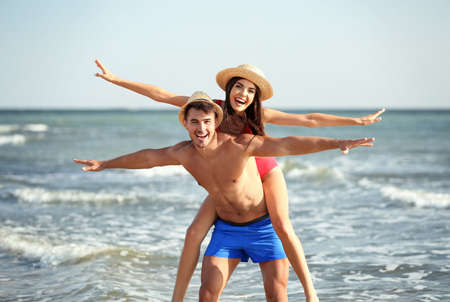 Photo for Happy young couple having fun at beach on sunny day - Royalty Free Image
