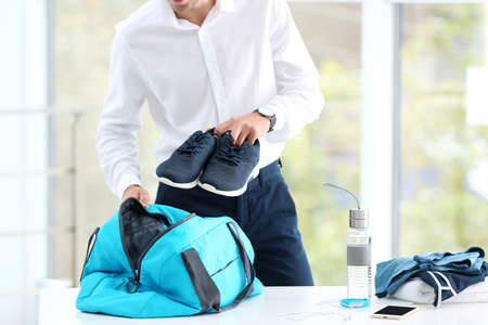 Photo pour Young businessman packing sports stuff for training into bag in office - image libre de droit