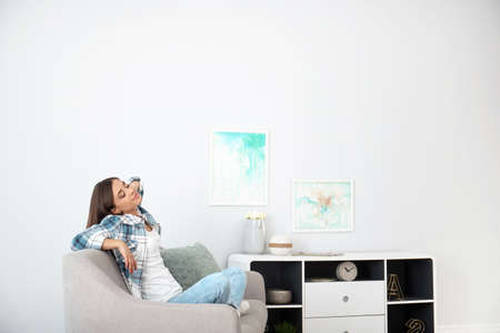 Photo pour Young woman relaxing under air conditioner at home - image libre de droit