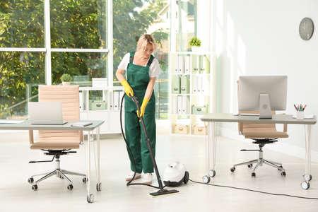 Foto de Female janitor in uniform cleaning office floor - Imagen libre de derechos