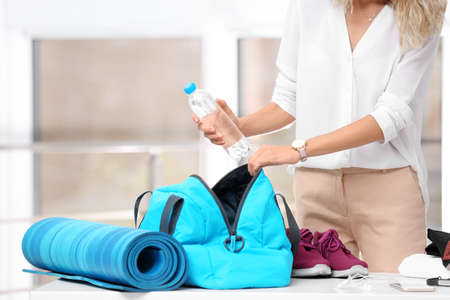 Photo pour Young businesswoman packing sports stuff for training into bag in office - image libre de droit