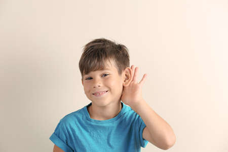 Foto de Cute little boy with hearing problem on light background - Imagen libre de derechos