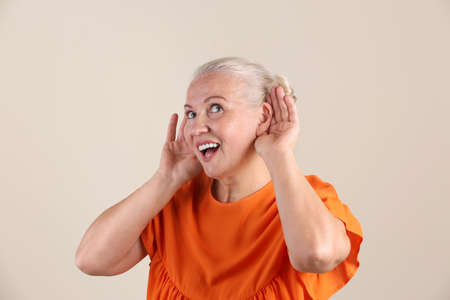 Foto de Mature woman with hearing problem on light background - Imagen libre de derechos