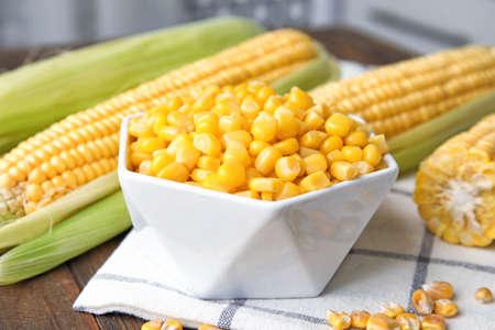 Photo pour Bowl with corn kernels on wooden table - image libre de droit