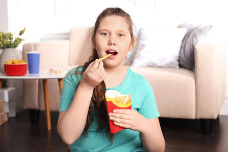 Photo for Overweight girl eating french fries indoors - Royalty Free Image
