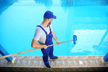 Photo pour Male worker cleaning outdoor pool with scoop net - image libre de droit