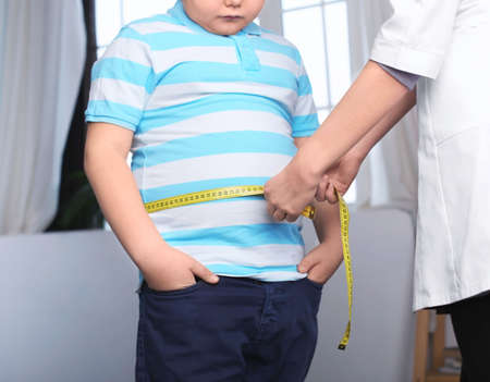 Photo pour Doctor measuring overweight boy in clinic - image libre de droit
