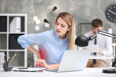 Photo pour Young woman suffering from back pain at table in office - image libre de droit