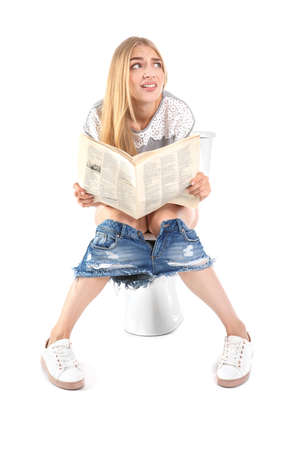 Foto de Young woman reading newspaper while sitting on toilet bowl. Isolated on white - Imagen libre de derechos
