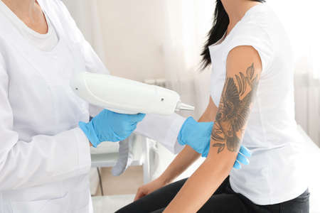Photo for Woman undergoing laser tattoo removal procedure in salon - Royalty Free Image