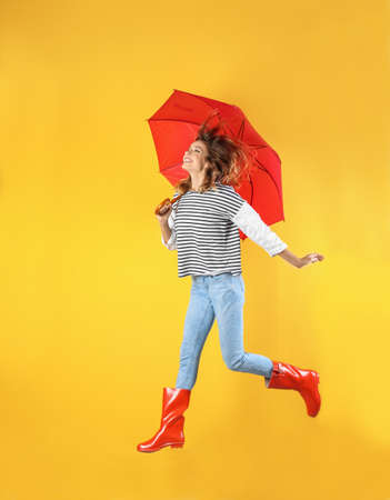 Photo pour Woman with red umbrella near color wall - image libre de droit
