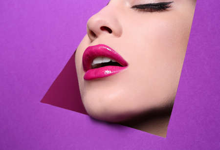 Photo pour View of beautiful young woman with perfect lips makeup through cutout in color paper - image libre de droit