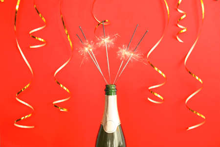 Photo pour Creative composition with bottle of champagne and sparklers on color background - image libre de droit