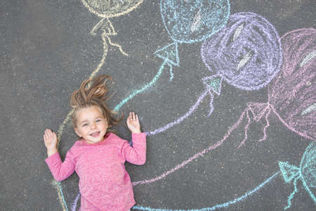 Photo for Little child lying near chalk drawing of balloons on asphalt, top view - Royalty Free Image