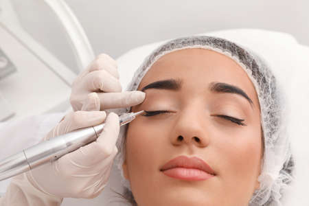 Foto de Young woman undergoing procedure of permanent eye makeup in tattoo salon, closeup - Imagen libre de derechos