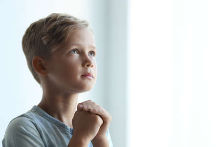 Foto de Little boy with hands clasped together for prayer on light background. Space for text - Imagen libre de derechos
