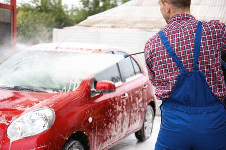 Foto de Male worker cleaning vehicle with high pressure water jet at car wash - Imagen libre de derechos
