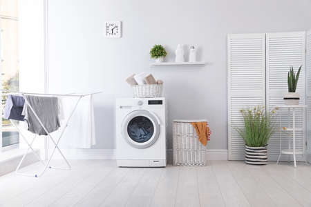 Photo pour Laundry room interior with washing machine near wall - image libre de droit