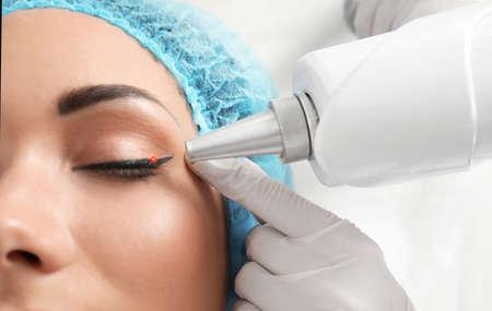 Foto de Woman undergoing laser tattoo removal procedure in salon, closeup - Imagen libre de derechos