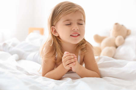 Photo pour Little girl praying in bed at home - image libre de droit