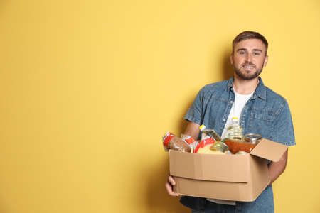 Foto de Young man holding box with donations on color background. Space for text - Imagen libre de derechos
