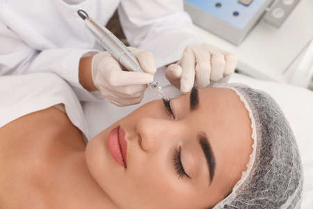 Foto de Young woman undergoing procedure of permanent eye makeup in tattoo salon, closeup - Imagen libre de derechos