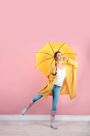 Foto de Woman with yellow umbrella near color wall - Imagen libre de derechos