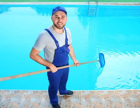 Foto de Male worker cleaning outdoor pool with scoop net - Imagen libre de derechos