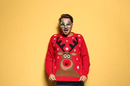 Photo pour Young man in Christmas sweater with party glasses on color background - image libre de droit