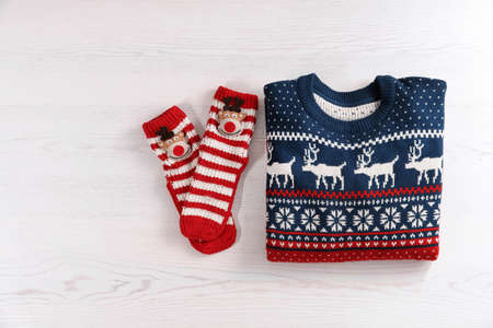 Photo pour Christmas sweater and socks with pattern on wooden background, top view - image libre de droit