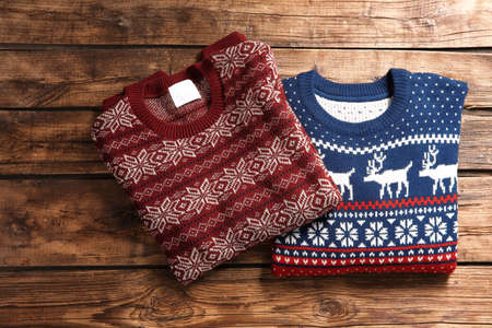 Photo pour Christmas sweaters with pattern on wooden background, top view - image libre de droit