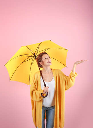 Foto de Woman with yellow umbrella on color background - Imagen libre de derechos