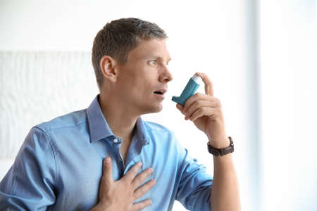 Photo pour Young man using asthma inhaler at home - image libre de droit