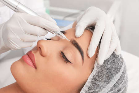 Photo pour Young woman undergoing procedure of permanent eyebrow makeup in tattoo salon, closeup - image libre de droit