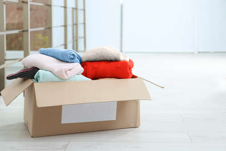 Photo for Donation box with clothes on floor indoors. Space for text - Royalty Free Image