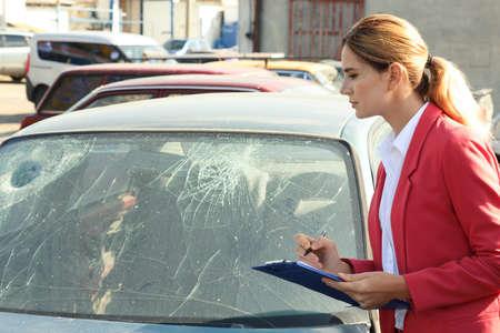 Photo pour Insurance agent filling claim form near broken car outdoors - image libre de droit