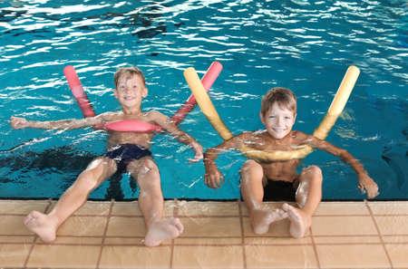 Photo pour Little boys with swimming noodles in indoor pool - image libre de droit