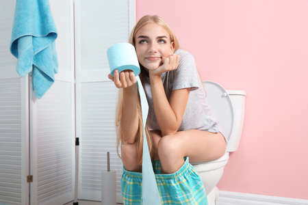 Foto de Woman with paper roll sitting on toilet bowl in bathroom - Imagen libre de derechos