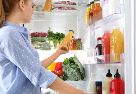 Photo pour Woman taking bottle with juice out of refrigerator in kitchen - image libre de droit