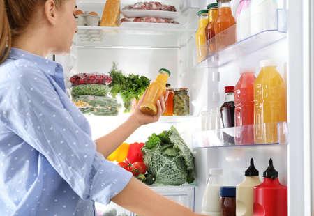 Foto de Woman taking bottle with juice out of refrigerator in kitchen - Imagen libre de derechos