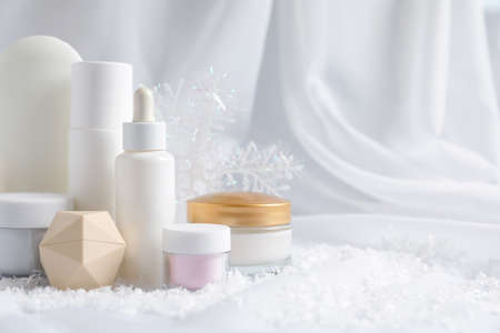 Photo pour Set of cosmetic products and decorative snow on white fabric, space for text. Winter care - image libre de droit