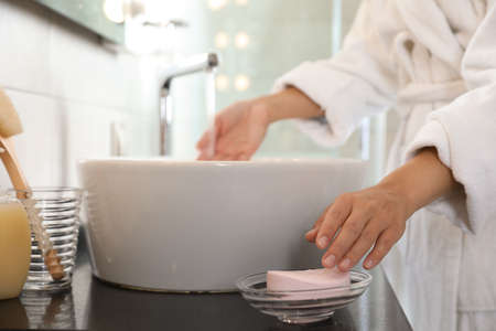 Foto de Young woman taking soap bar to wash hands in bathroom, closeup - Imagen libre de derechos