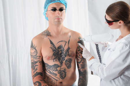 Photo for Man undergoing laser tattoo removal procedure in salon - Royalty Free Image