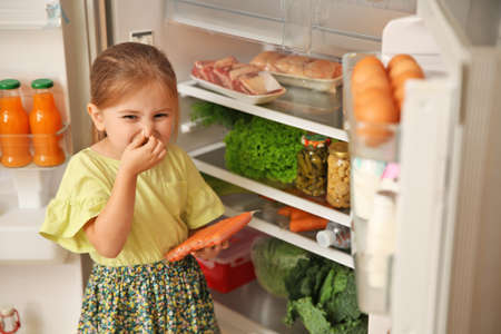 Foto de Cute little girl with bad smelling sausages near refrigerator at home - Imagen libre de derechos