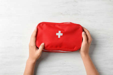 Photo pour Woman holding first aid kit on wooden background, top view - image libre de droit