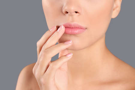 Foto de Closeup view of beautiful young woman on grey background. Lips contouring, skin care and cosmetic surgery concept - Imagen libre de derechos