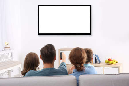 Photo pour Family with remote control sitting on couch and watching TV at home, space for design on screen. Leisure and entertainment - image libre de droit