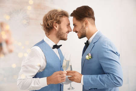 Foto de Happy newlywed gay couple with glasses of champagne at home - Imagen libre de derechos