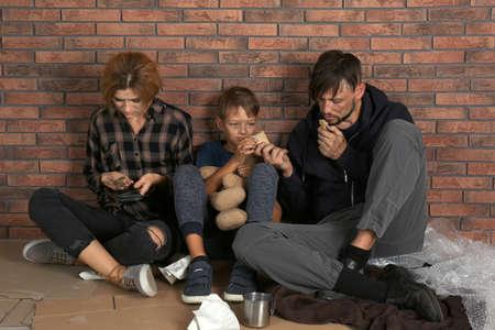 Foto de Poor homeless family sitting on floor near brick wall - Imagen libre de derechos